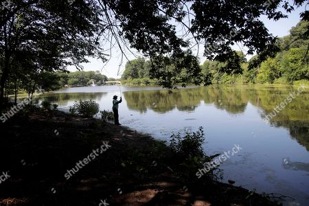 Chevelle Thornton, of Orange, N.J., casts his line while fishing at Branch Brook Park after getting off work from his job at Amazon, in Newark, N.J