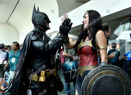 Armando Abarca, Jessica Rose Davis. Armando Abarca, left, dressed as Batman, and Jessica Rose Davis, dressed as Wonder Woman, of Los Angeles, high five each other as they attend day one of Comic-Con International, in San Diego