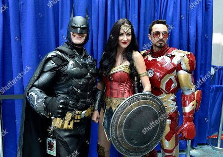 Armando Abarca, Jessica Rose Davis, Guillermo Gonzalez. Armando Abarca, dressed as Batman, left, and Jessica Rose Davis, dressed as Wonder Woman, center, of Los Angeles, and Guillermo Gonzalez, of Sacramento, Calif., dressed as Iron Man, attend day one of Comic-Con International, in San Diego
