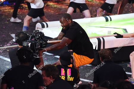 Former NFL player Martellus Bennett participates in the Crest strong kid challenge at the Kids' Choice Sports Awards at the Barker Hangar, in Santa Monica, Calif