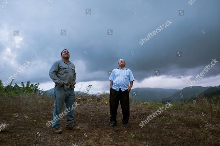 "Retired resident Ramon Serrano, right, stands outside his home with a lineman from the Puerto Rico Power Authority as they watch a man restore power which was cut off by Hurricane Irma and Maria in Adjuntas, Puerto Rico. For the first time in 10 months, Serrano watched the 11 o'clock news on a recent weeknight and went to bed at midnight with his wife. ""It's the latest we've stayed up,"" said the 77-year-old"