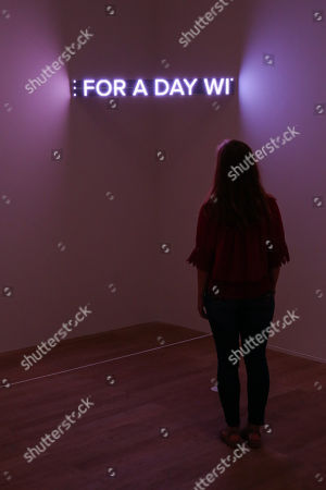 A staff member looks at LED text sculpture.