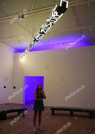 A staff member looks at a LED text sculpture, the artist's iconic Truism series and FLOOR (2015), a large-scale, kaleidoscopic work which will be mounted to the ceiling for the first time.