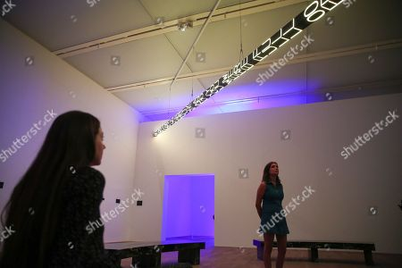 Staff members look at a LED text sculpture, the artist's iconic Truism series and FLOOR (2015), a large-scale, kaleidoscopic work which will be mounted to the ceiling for the first time.
