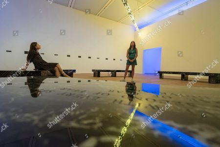 """Staff members view """"FLOOR 2015"""", a large scale kaleidoscopic work, by Jenny Holzer at the preview of ARTIST ROOMS: Jenny Holzer at Tate Modern."""