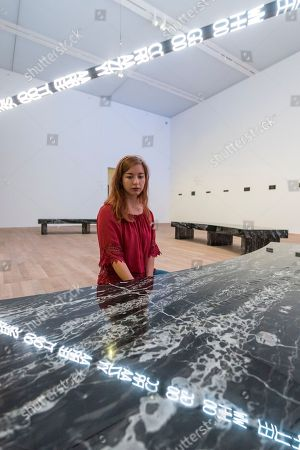 """A staff member views """"FLOOR 2015"""", a large scale kaleidoscopic work, by Jenny Holzer at the preview of ARTIST ROOMS: Jenny Holzer at Tate Modern."""