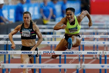 Queen Harrison of the US, right, races ahead Eline Berings from Belgium, during the women's 100 m hurdles race of the IAAF Diamond League Athletics meeting at the Louis II Stadium in Monaco