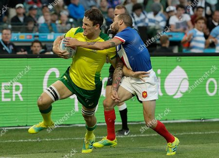 Australia's Lachie Anderson, left, runs against France's Terry Bouhraoua during the Rugby Sevens World Cup in San Francisco