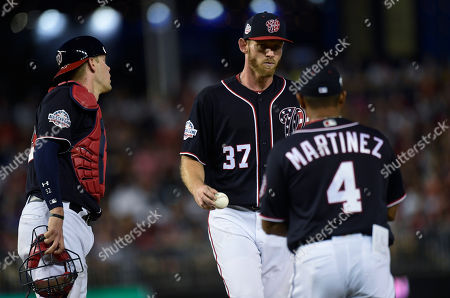 Stephen Strasburg, Jamie Burke, Dave Martinez. Washington Nationals starting pitcher Stephen Strasburg (37) hands the ball to manager Dave Martinez, (4) as he is pulled from a baseball game as catcher Jamie Burke, left, watches during the fifth inning against the Atlanta Braves at Nationals Park in Washington