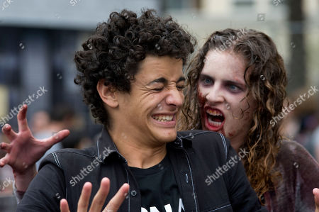Josh Thomas reacts as he poses for a photograph with a woman dressed as a zombie in a Walking Dead interactive area on the second day of Comic Con International in San Diego, California, USA, 20 July 2018.