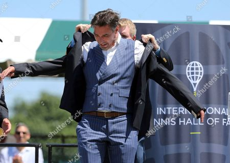 Tennis Hall of Fame inductee, Michael Stich, of Germany, receives his jacket during ceremonies at the International Tennis Hall of Fame, in Newport, R.I