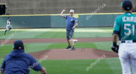 Pearl Jam guitarist Mike McCready, center, throws out the first pitches of a baseball game between the Seattle Mariners and the Chicago White Sox at Safeco Field in Seattle. Pearl Jam is scheduled to play two concerts in August at the ballpark
