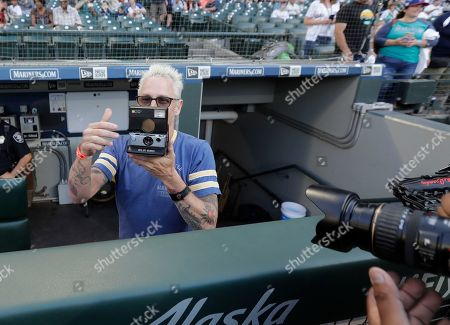 Pearl Jam guitarist Mike McCready holds his Polaroid instant camera before throwing out the first pitch of a baseball game between the Seattle Mariners and the Chicago White Sox, in Seattle