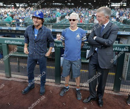 Eddie Vedder, left, lead singer of the rock band Pearl Jam, and Pearl Jam guitarist Mike McCready, center, stand with Seattle Mariners President Kevin Mather, right, before McCready and Vedder threw out the first pitches of a baseball game between the Seattle Mariners and the Chicago White Sox at Safeco Field in Seattle. Pearl Jam is scheduled to play two concerts in August at the ballpark