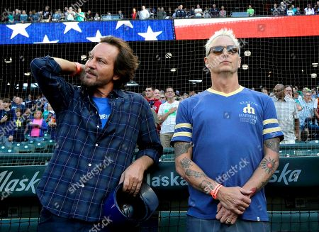Eddie Vedder, left, lead singer of the rock band Pearl Jam, and Pearl Jam guitarist Mike McCready, right, stand during the singing of the national anthem before a baseball game between the Seattle Mariners and the Chicago White Sox at Safeco Field in Seattle. Pearl Jam is scheduled to play two concerts in August at the ballpark