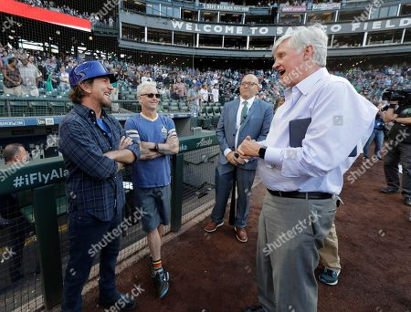 Eddie Vedder, left, lead singer of the rock band Pearl Jam, and Pearl Jam guitarist Mike McCready, second from left, stand with Mariners owner John Stanton, right, before McCready and Vedder threw out the first pitches of a baseball game between the Seattle Mariners and the Chicago White Sox at Safeco Field in Seattle. Pearl Jam is scheduled to play two concerts in August at the ballpark