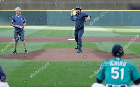Eddie Vedder, upper right, lead singer of the rock band Pearl Jam, and Pearl Jam guitarist Mike McCready, left, throw out the first pitches of a baseball game between the Seattle Mariners and the Chicago White Sox at Safeco Field in Seattle. Pearl Jam is scheduled to play two concerts in August at the ballpark