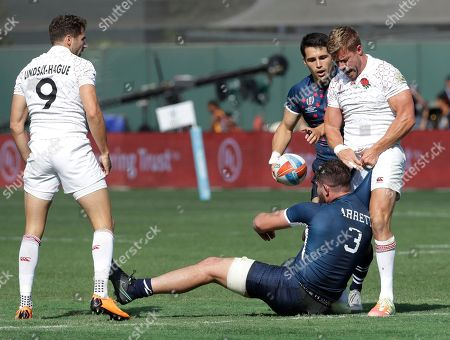 Stock Image of England's Tom Mitchell, right, pulls on the jersey of United States's Dan Barrett, below, as teammate Ollie Lindsay-Hague, left, looks on during the Rugby Sevens World Cup in San Francisco