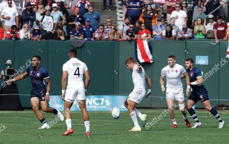 England's Tom Mitchell, center, kicks the ball to England's Phil Burgess to score against the United States during the Rugby Sevens World Cup in San Francisco