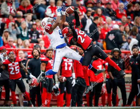 Montreal Alouettes' Ernest Jackson, left, goes up for a pass as Calgary Stampeders' Jamar Wall, defends during first-quarter CFL football game action in Calgary, Alberta