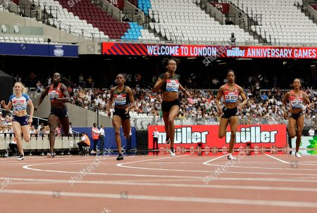Stephenie Ann McPherson of Jamaica, center, crosses the finish line to win the women's 400 meters race at the IAAF Diamond League athletics meeting at London Stadium in London