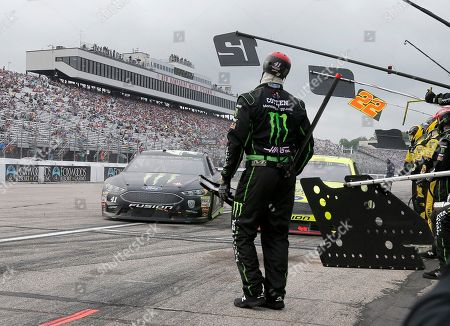 A member of the Kurt Busch's pit crew pauses while Busch hesitates to pass Ryan Blaney in the pits during the NASCAR Cup Series auto race, at New Hampshire Motor Speedway in Loudon, N.H