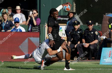 New Zealand's Joe Ravouvou, top, runs against England's Tom Mitchell during the Rugby Sevens World Cup championship final in San Francisco, . New Zealand won 33-12