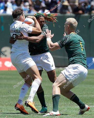 Stock Photo of England's Ollie Lindsay-Hague, left, is tackled by South Africa's Justin Geduld, center, as Ryan Oosthuizen (1) approaches during a Rugby Sevens World Cup semifinal in San Francisco, . England won 29-7