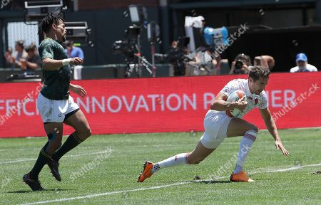 England's Ollie Lindsay-Hague, right, scores in front of South Africa's Selvyn Davids during a Rugby Sevens World Cup semifinal in San Francisco, . England won 29-7
