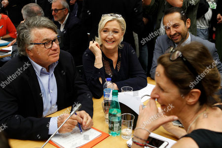 French Member of Parliament and president of the far-right 'Rassemblement National' party, Marine Le Pen, second left, flanked with deputy Gilbert Collard, left, attends the hearing of French Interior Minister Gerard Collomb with the deputies of the Laws Commission concerning the case of President Macron's security aide Alexandre Benalla, at the National Assembly in Paris, France, . Investigators have detained for questioning on Friday, July 20, 2018 one of President Emmanuel Macron's top security aides caught on camera beating a protester in May, a turn of events now evolving into a major political crisis for the president