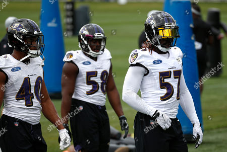 Baltimore Ravens linebacker C.J. Mosley, right, walks in front of teammates Kenny Young (40) and Alvin Jones during an NFL football training camp practice at the team's headquarters, in Owings Mills, Md
