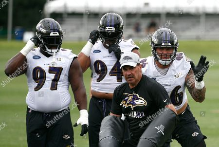 Baltimore Ravens defensive end Brent Urban, right, runs a drill in front of teammates Michael Pierce (97) and Carl Davis during an NFL football training camp practice at the team's headquarters, in Owings Mills, Md