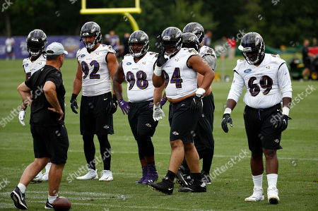 Baltimore Ravens defensive end Bronson Kaufusi (92), defensive tackle Brandon Williams (98), defensive tackle Carl Davis (94) and defensive tackle Willie Henry (69) stand on the field during an NFL football training camp practice at the team's headquarters, in Owings Mills, Md