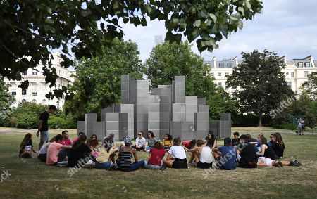 A group of tourists sits in front of Conrad Shawcross' sculpture 'Optic Labyrinth'  (2018) at the Frieze Sculpture Park 2018 at Regents Park in London, Britain, 23 July 2018. The sculpture park runs until 07 October 2018.