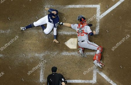 Washington Nationals catcher Jamie Burke tags out Milwaukee Brewers' Hernan Perez at home during the fourth inning of a baseball game, in Milwaukee