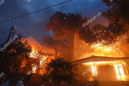 A house is set alight by the forest fire in Neos Voutzas area, Greece