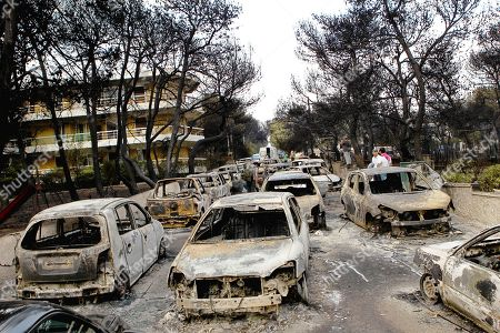 People stand amid the charred remains of burned-out cars in Mati east of Athens