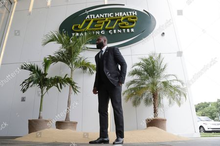 Former New York Jets cornerback Darrelle Revis stands in front of a makeshift island at the main entrance to the team's training facility after a news conference officially announcing his retirement, in Florham Park, N.J. Revis leaves behind an 11-season career that included four All-Pro selections and a Super Bowl win with the New England Patriots