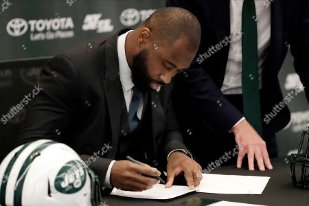 Former New York Jets cornerback Darrelle Revis signs a one-day contract with the Jets during a news conference officially announcing his retirement from NFL football, in Florham Park, N.J. Revis leaves behind an 11-season career that included four All-Pro selections and a Super Bowl win with the New England Patriots