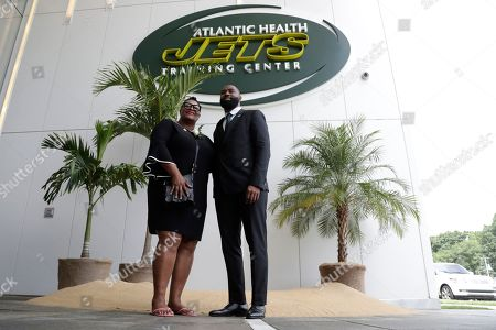 Former New York Jets cornerback Darrelle Revis, right, poses for photos with his mother, Diana Gilbert, in front of a makeshift island at the main entrance to the team's training facility after a news conference officially announcing his retirement, in Florham Park, N.J. Revis leaves behind an 11-season career that included four All-Pro selections an a Super Bowl win with the New England Patriots