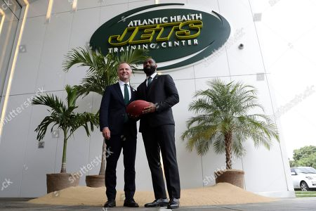 Stock Photo of Former New York Jets cornerback Darrelle Revis, right, poses for photos with team owner Christopher Johnson after a news conference officially announcing his retirement from NFL football, in Florham Park, N.J. Revis leaves behind an 11-season career that included four All-Pro selections an a Super Bowl win with the New England Patriots