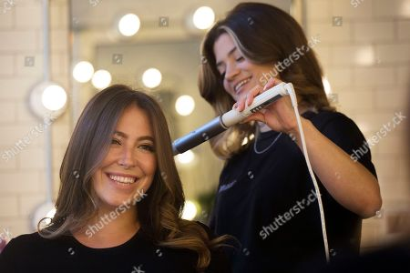 Stock Picture of Hair salon owner Erika Wasser, left, has her hair touched up by lead stylist Samantha Sheppard at a Glam+Go studio, in New York. Wasser owns nine salons in three cities