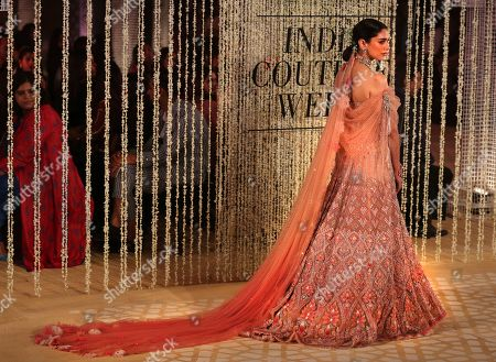 Bollywood actress Aditi Rao Hydari displays a creation of Indian designer Tarun Tahiliani during India Couture Week in New Delhi, India, . The five day show is showcasing some of the top designers of India
