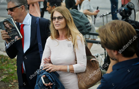 Stanley Zareff, left, holds a book called Captive, authored by actress Catherine Oxenberg, center, as they leave federal court in Brooklyn, in New York. Oxenberg's daughter India has been named in a criminal complaint against an upstate New York group called NXIVM, accused of branding some of its female followers and forcing them into unwanted sex
