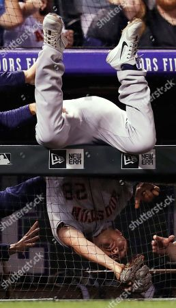 J D Davis, r m. Houston Astros third baseman J.D. Davis ends up draped over the dugout rail after catching a pop foul by Colorado Rockies' Nolan Arenado during the seventh inning of a baseball game, in Denver. The Rockies won 3-2