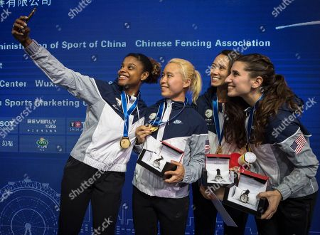 Stock Picture of (L-R) Nzingha Prescod, Margaret Lu, Lee Kiefer and Nicole Ross from the USA celebrate their gold medals after the Women's Team Foil final match against Italy at the Fencing World Championships in Wuxi, China, 26 July 2018.