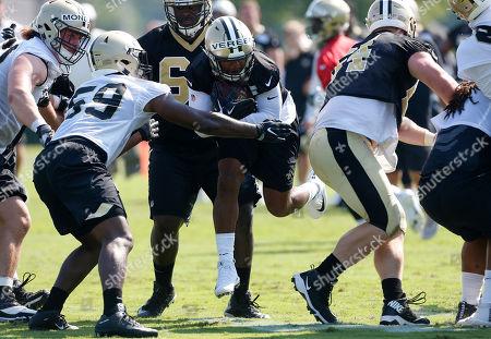 New Orleans Saints running back Shane Vereen, center, runs the ball as linebacker KeShun Freeman (59) defends during NFL football practice in Metairie, La