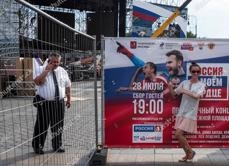 Stock Picture of A tourist poses in front of a poster shows Russian soccer players goalkeeper Igor Akinfeev, top, Sergei Ignashevich, center, and Artyom Dzyuba as a member of security speaks on the phone in Manezhnaya Square near the Kremlin in Moscow, Russia