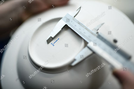 A staff worker measures the placement of the KPM logo at the Royal Porcelain Factory 'Koenigliche Porzellan-Manufaktur' (KPM) in Berlin, Germany, 26 July 2018. The name Royal Porcelain Factory 'Koenigliche Porzellan-Manufaktur' (KPM) exists since 1763, when King Frederick II of Prussia took over the company from a businessman. Nowadays the company is run by Berlin banker Joerg Woltmann.