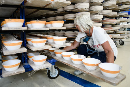 Staff worker Heike Rossmeisl places a plank with prepared bowls at the Royal Porcelain Factory 'Koenigliche Porzellan-Manufaktur' (KPM) in Berlin, Germany, 26 July 2018. The name Royal Porcelain Factory 'Koenigliche Porzellan-Manufaktur' (KPM) exists since 1763, when King Frederick II of Prussia took over the company from a businessman. Nowadays the company is run by Berlin banker Joerg Woltmann.